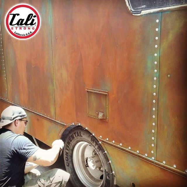 Krystiano D'Costa installing rivets on a 1969 vintage Dodge RV